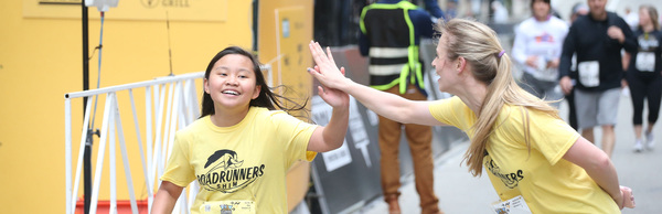 Young girl running gives high-five to young woman