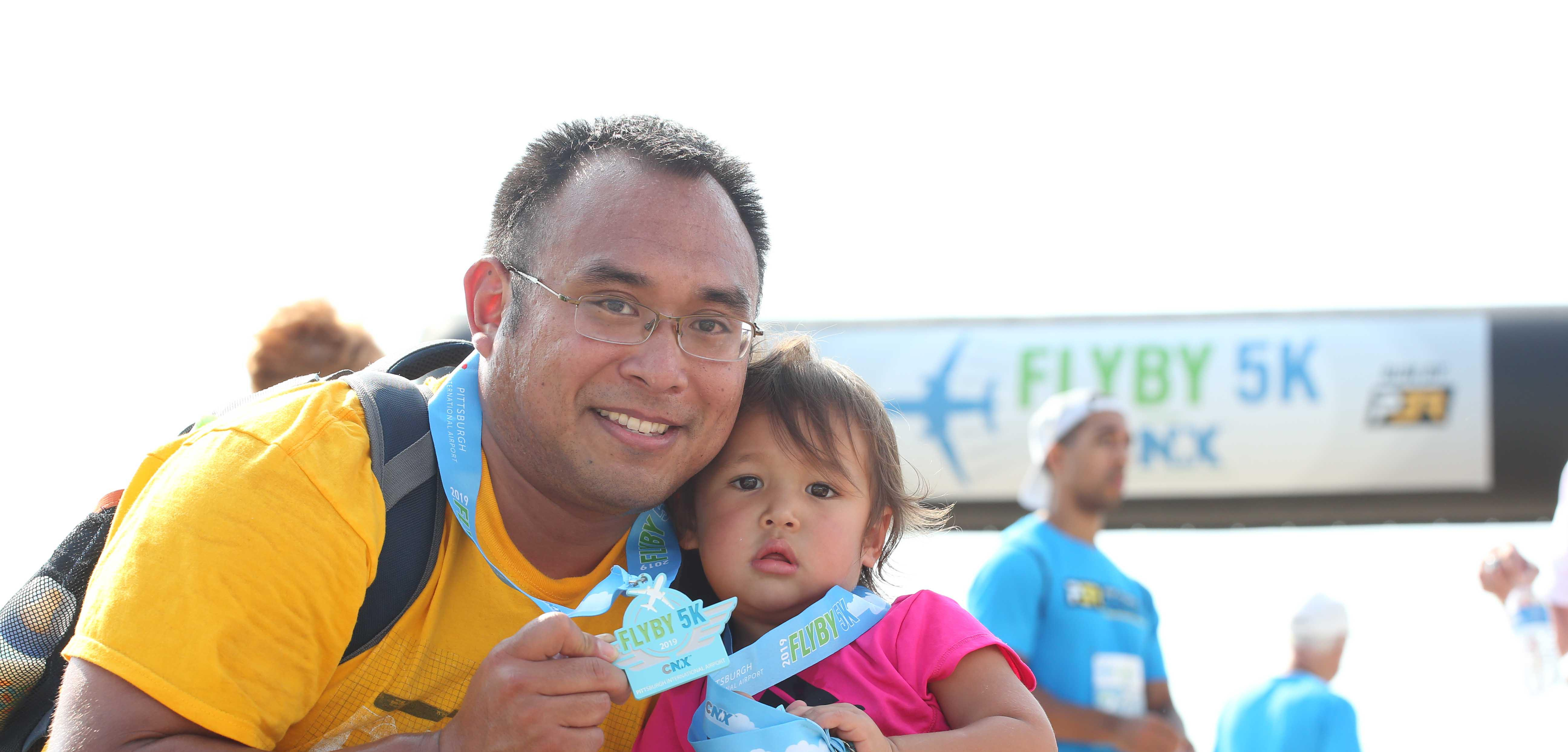 middle-aged man holding very young child as they smile with their Fly By 5K medals