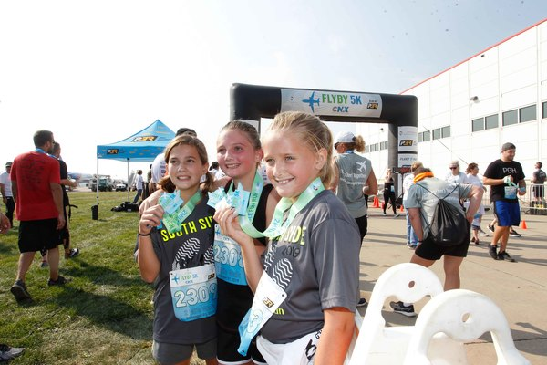 3 young girls participating in FlyBy 5K and 2-Mile Fun Run/Walk