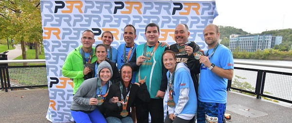 Group of runners posing together with their race medals after finishing the GAP Relay presented by UPMC Health Plan