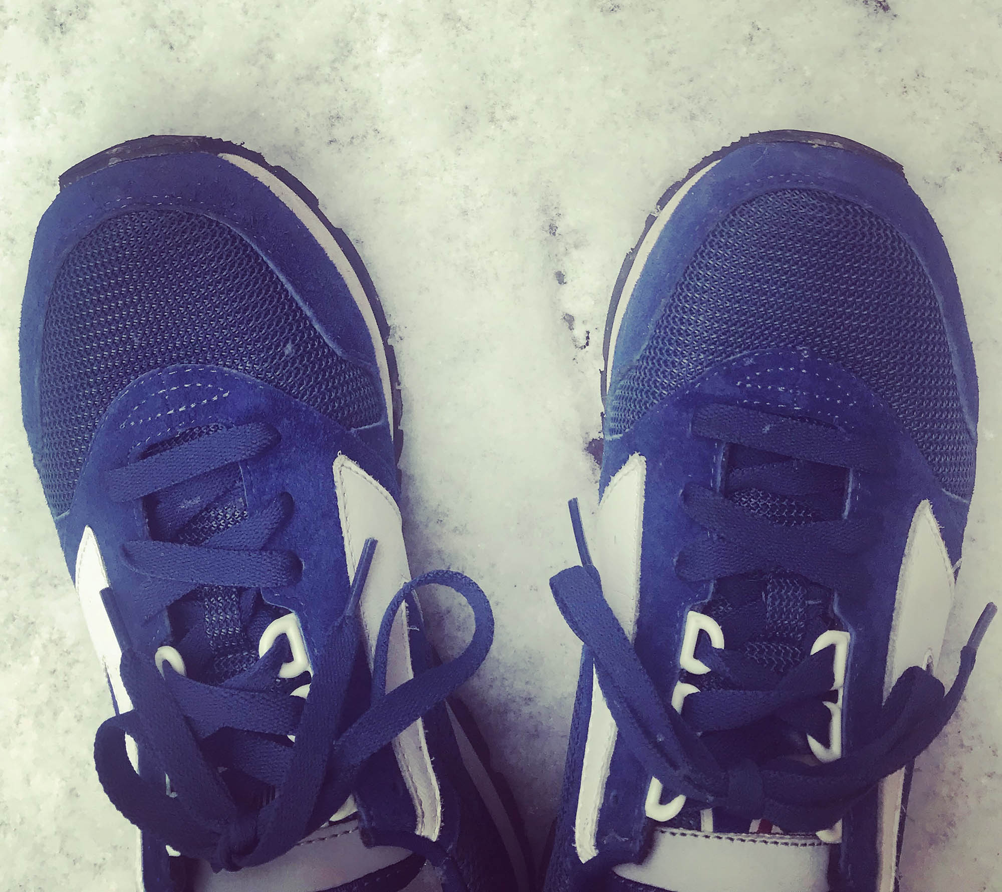 blue sneakers set down on snowy ground