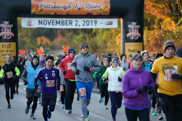 Large group of people running from the start line of the EQT Pittsburgh 10 Miler race