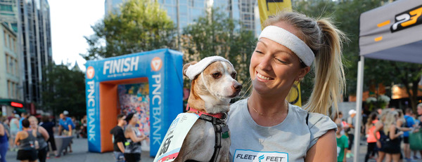 Woman holding her dog near the finish line of the Fleet Feet Liberty Mile race
