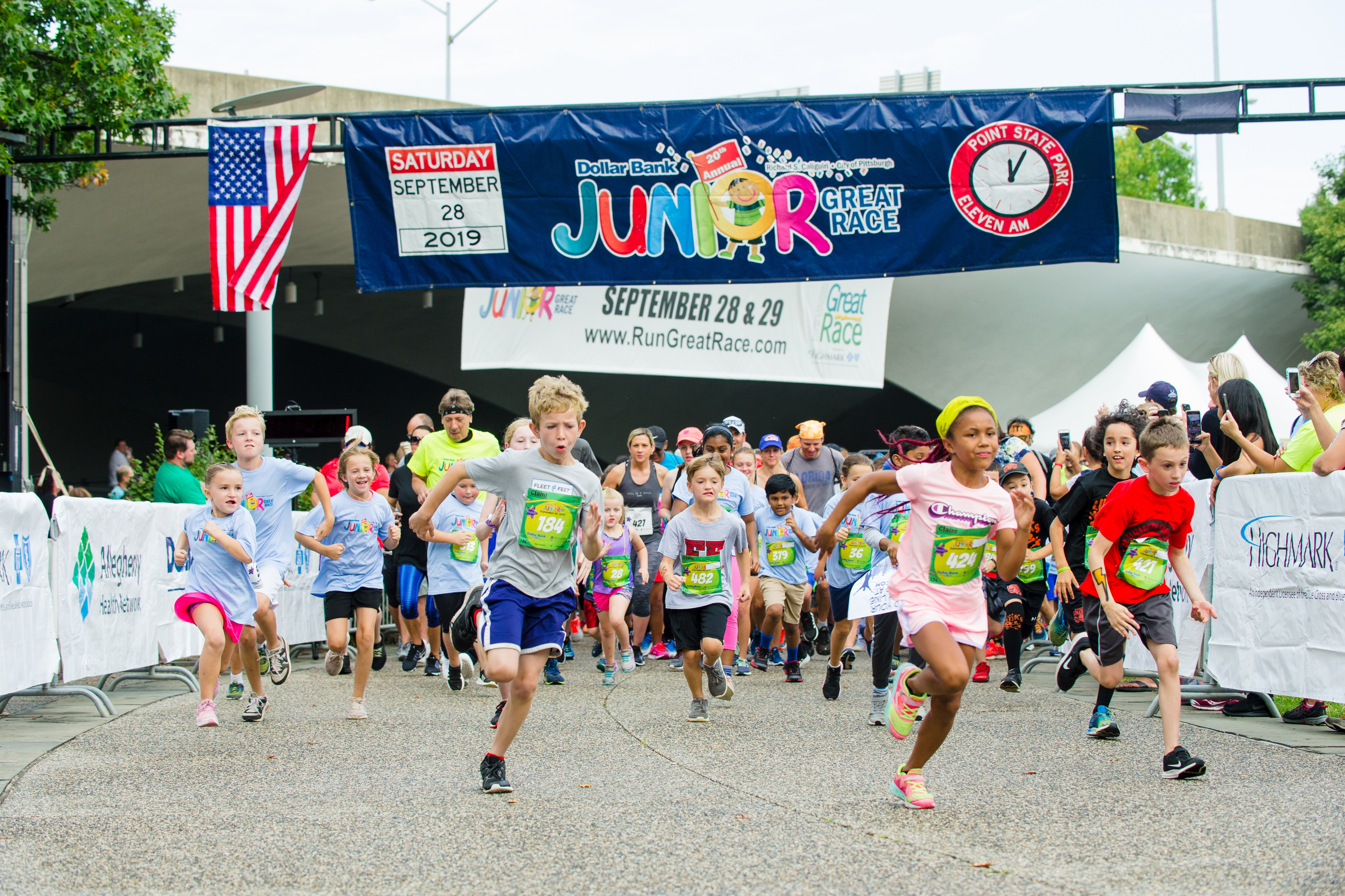 A large group of children running in the Dollar Bank Junior Great Race, which consists of the One-Mile Family Fun Run, Tot Trot, and Diaper Dash